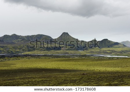 Moss field with volcanic crater in a distance on a cloudy day, lakagigar, Iceland  - stock photo