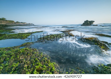 Moss On the Rock  with strong water wave at Low Tide Beach in Bali. Taken during sunset.