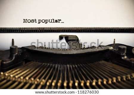 "Most popular. Really old typewriter. Focus on the text ""Most popular"" written on the sheet of paper. - stock photo"