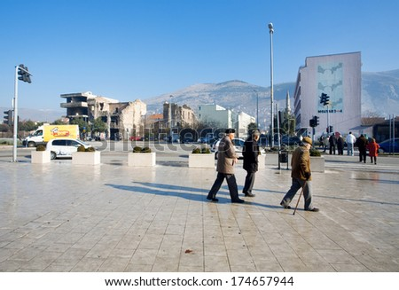 MOSTAR, BOSNIA AND HERZEGOVINA - DEC 28: Seniors walk down the street with houses destroyed during the Bosnian war on December 28 2013. 45% of the country's population are Muslims, 36% are Orthodox - stock photo