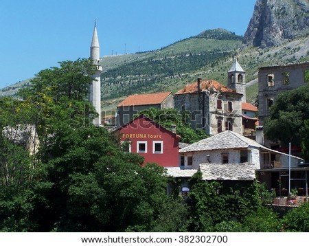 MOSTAR, BOSNIA - JUNE 23, 2008: Buildings on the hill, with the minaret of Koski Mehmed pasa Mosque visible