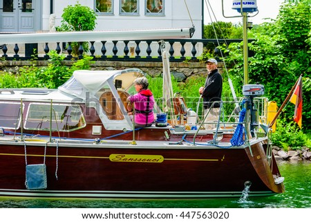 Motala, Sweden - June 21, 2016: Senior couple on a sailboat. Woman wears a life jacket, male do not. Real life situation.