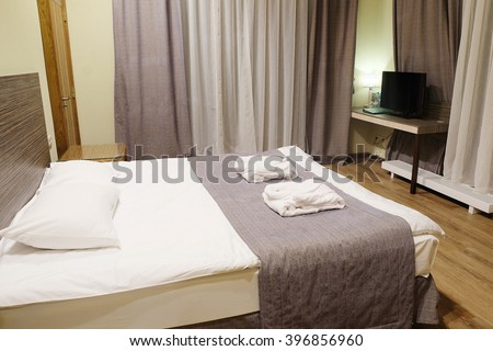 Motel room with queen-size bed - stock photo