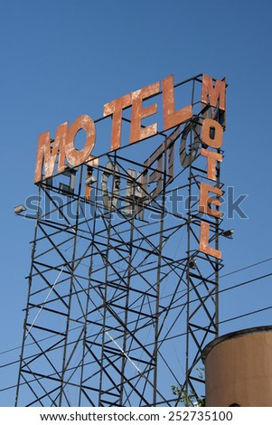 motel rusted sign on blue sky background - stock photo