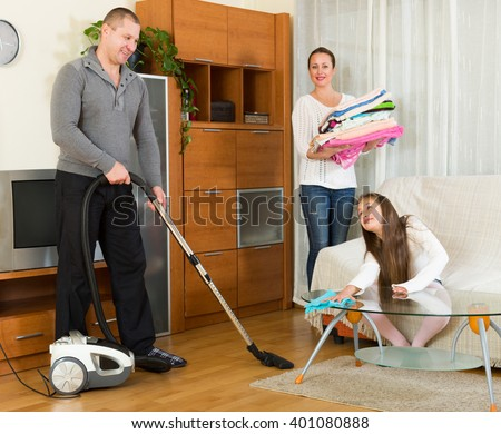 Mother,american father and cute girl doing general cleaning indoors