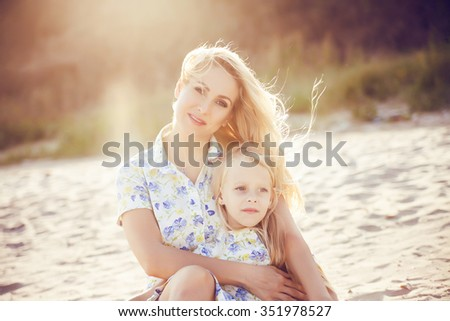 Mother and a beautiful blonde little girl sitting on the beach at a tropical resort. The concept of rest. Beautiful dress with blue and green flowers