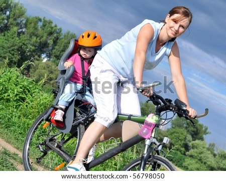 Mother and a daughter cycling - stock photo