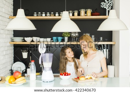 Mother and a daughter preparing fruits for smoothie - stock photo