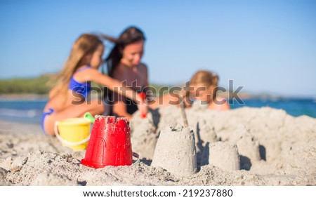 Mother and adorable little daughters playing with beach toys - stock photo