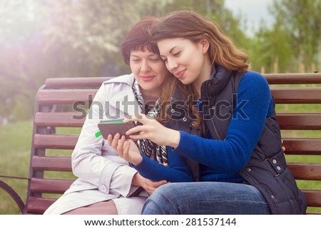 mother and adult daughter are doing Selfe outdoors
