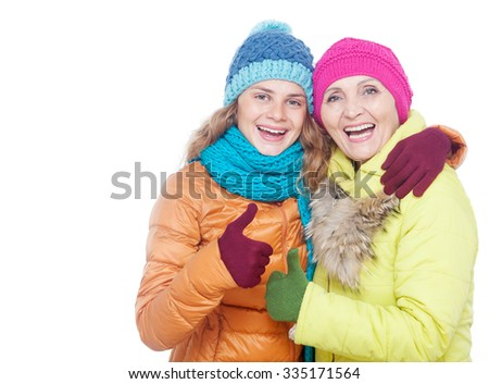 mother and adult daughter in the bright winter clothes isolated on white background