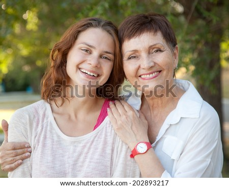 mother and adult daughter in the park, family portrait