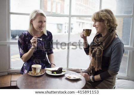 Mother And Adult Daughter Meeting In Coffee Shop