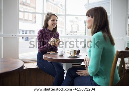 Mother And Adult Daughter Meeting In Coffee Shop - stock photo