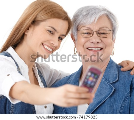 Mother and attractive young daughter photographing themselves by mobile phone, smiling happily.? - stock photo