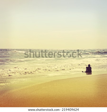 Mother and baby are sitting on empty beach. Vintage retro style - stock photo