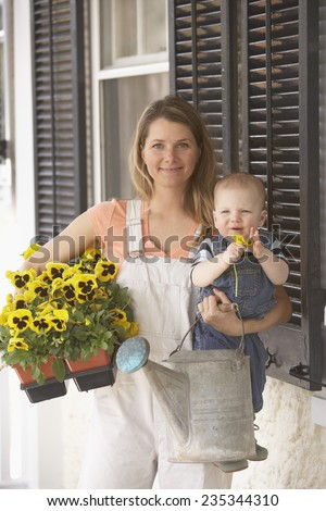 Mother and Baby Boy Preparing to Work in Garden - stock photo