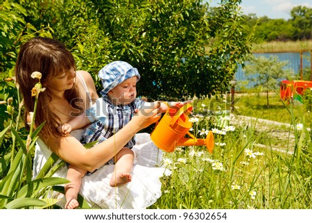 Mother and baby boy watering camomiles in garden - stock photo