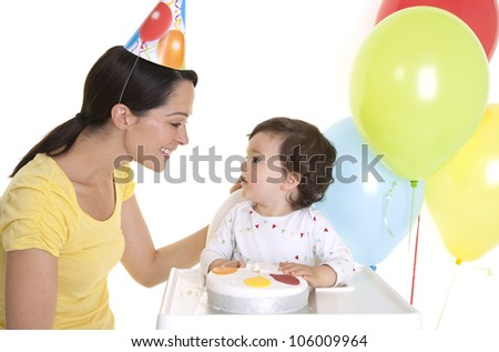 Mother and baby celebrating birthday at party - stock photo