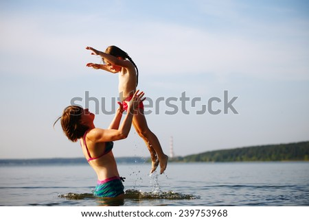 Mother and baby child playing in a sea - stock photo