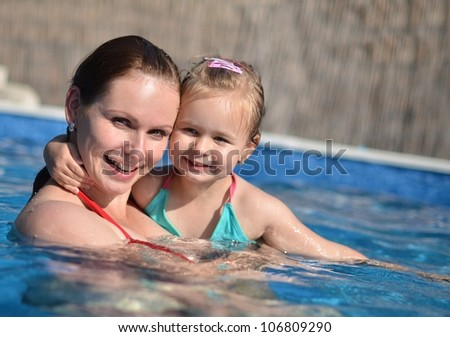 Mother and baby child playing in a swimming pool