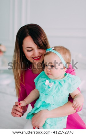 Mother and baby closeup portrait, happy faces,  adorable small girl, mom and kid having fun indoor, parents joy, holding little child, healthy toddler and mommy, happiness concept - stock photo