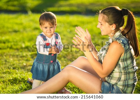Mother and baby daughter are playing outdoors. Young mom and her cute little baby-girl are having fun in the sunny garden. Happy childhood and motherhood concept.  - stock photo