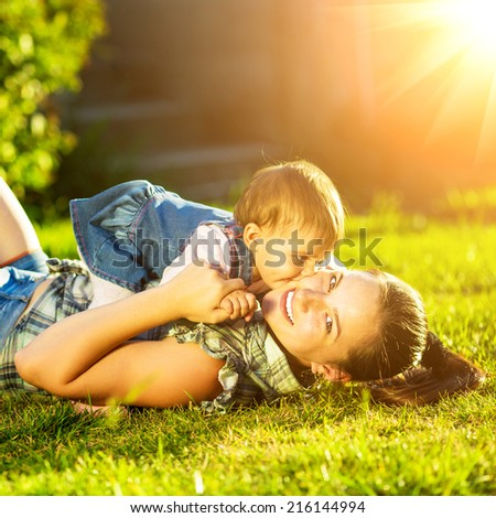 Mother and baby daughter are playing outdoors. Young mom and her cute little baby-girl are having fun in the sunny garden. Happy childhood and parenthood concept.  - stock photo