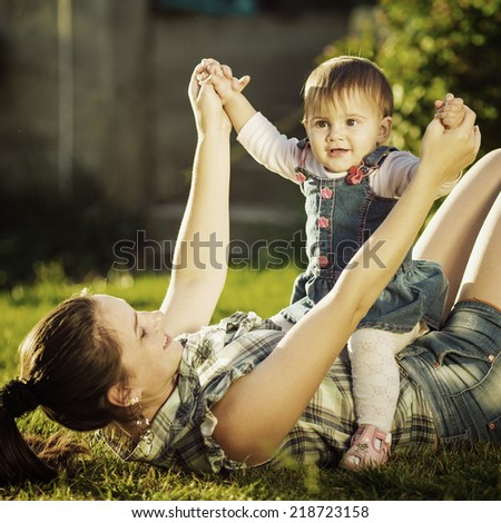 Mother and baby daughter are playing outdoors. Young mom and her cute little baby-girl are having fun in the sunny garden. Happy childhood and parenthood concept. Instagram style. - stock photo