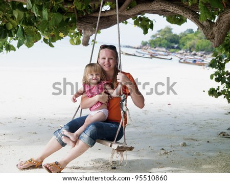 Mother and baby daughter on a beach swing. Koh Lipe island in Thailand.