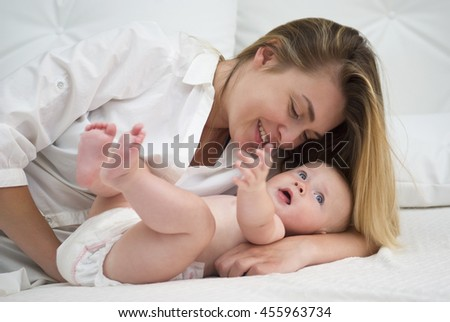 Mother and baby daughter on bed - stock photo