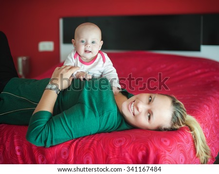 Mother and baby daughter on the bed - stock photo
