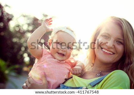 Mother and baby daughter outside
