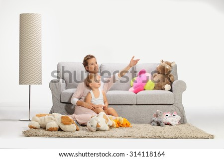 Mother and baby daughter playing in living room - stock photo