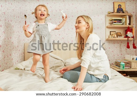 Mother and baby daughter plays at home on the sofa, room with icons - stock photo