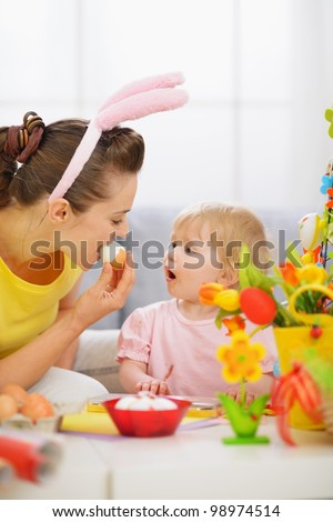 Mother and baby eating Easter egg - stock photo