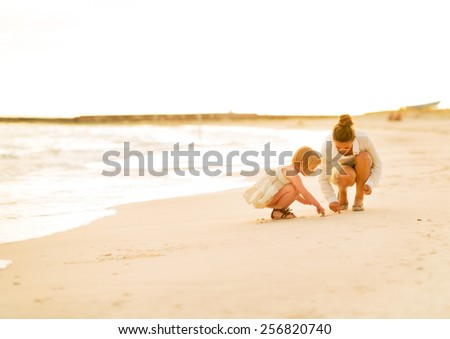 Mother and baby girl drawing on sand on beach at the evening - stock photo