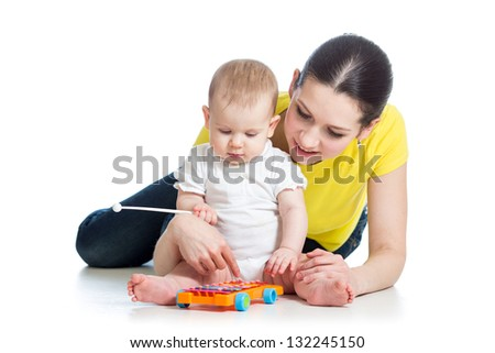 Mother and baby girl having fun with musical toy isolated - stock photo