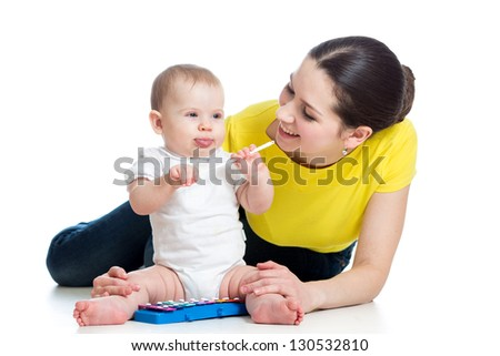 Mother and baby girl having fun with musical toy. Isolated on white background - stock photo