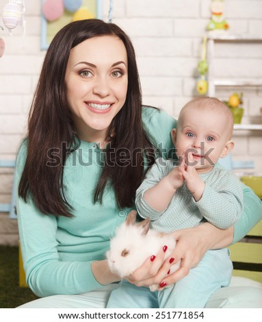 Mother and baby girl holding little Easter rabbit  - stock photo