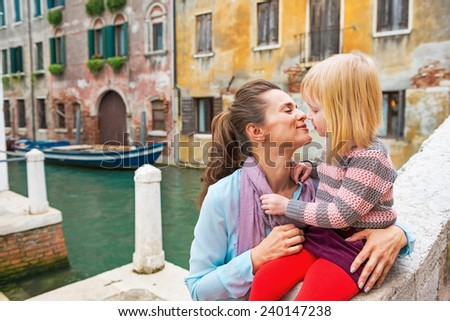 Mother and baby girl kissing in venice, italy - stock photo