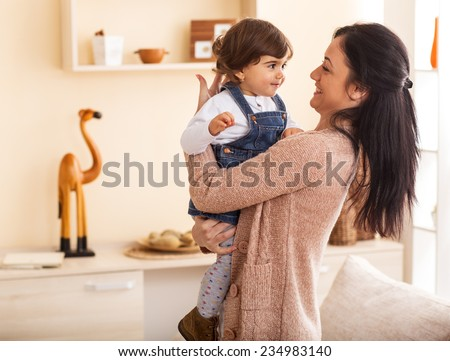 Mother and baby girl making fun in living room.Laughing.Mother holding her daughter. - stock photo