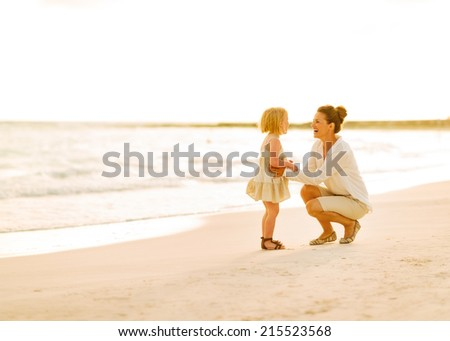 Mother and baby girl playing on the beach in the evening - stock photo