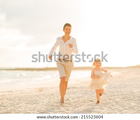 Mother and baby girl running on the beach in the evening - stock photo