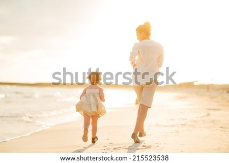 Mother and baby girl running on the beach in the evening. rear view - stock photo
