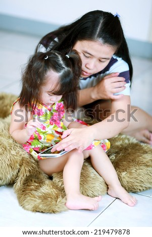 Mother and baby girl using tablet computer - stock photo