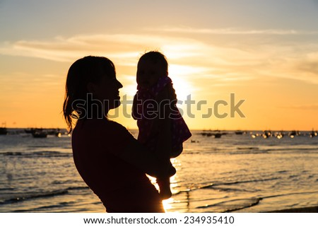 mother and baby having fun at sunset beach - stock photo