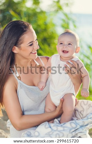 mother and baby having fun at the beach - stock photo