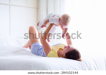 Mother and baby in bed. Young mom playing with her newborn son. Child and parent together at home. Family with kids in the morning. Woman relaxing with kid in a sunny bedroom. Happiness and motherhood - stock photo
