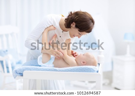 Mother and baby in diaper on changing table. Mom changing nappy on baby boy. Kids nursery. Infant hygiene and care products. Diapers for young children. Mother playing with child in white bedroom.